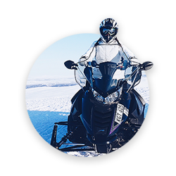 A man riding a snowmobile in winter