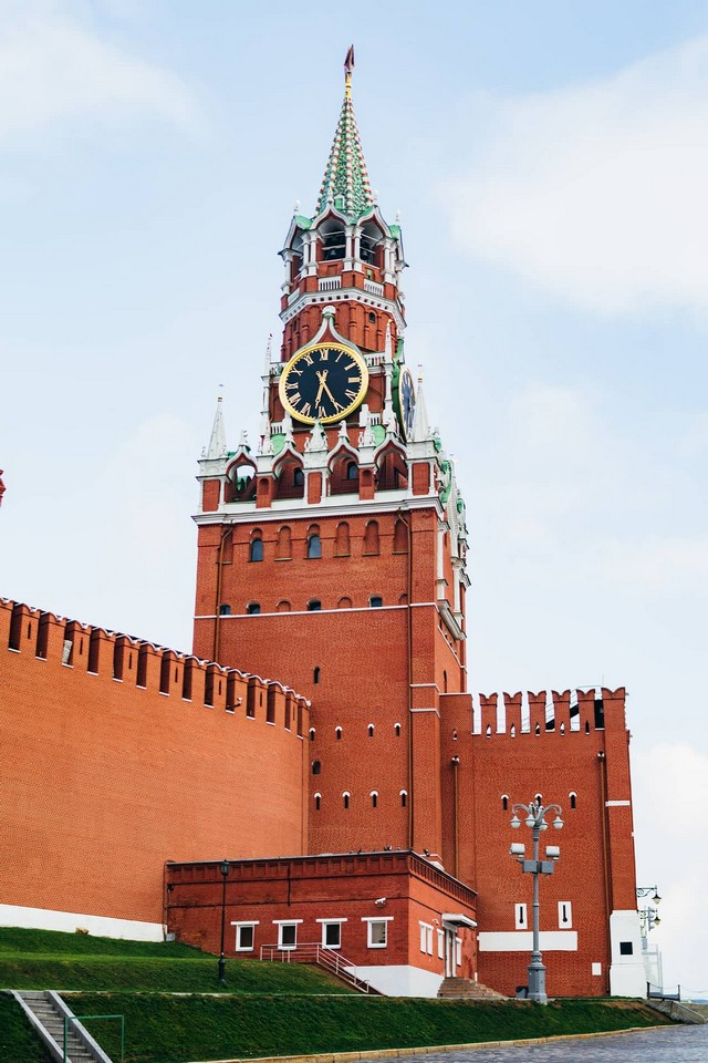 A high red brick clock tower with a star on the top of the spire