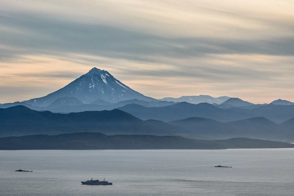 Highlands behind the sea, beautiful landscape with mountains and volcano, a ship in the sea