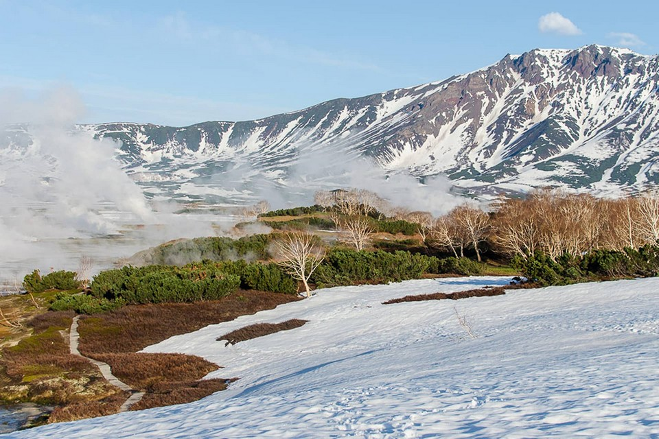 Geysers field in winter, hills and earth covered with snow