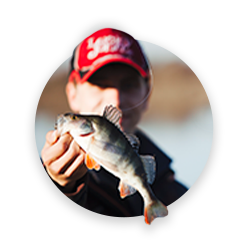 A man wearing a cap showing a fish in his hand