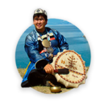A shaman in traditional clothing performing a ritual with a drum