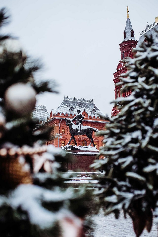 A red brick building and a bronze monument of a man riding a horse behind the snow covered spruces