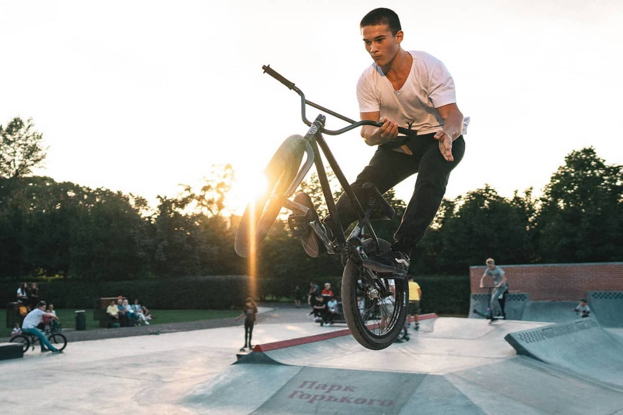A young man riding a mountain bike, performing a maneuver on a bicycle on bike park ramps