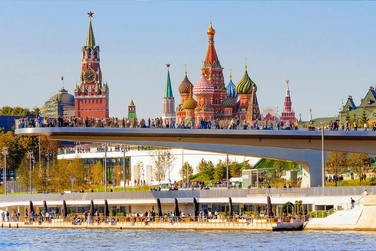 Moscow river embankment, panoramic observation deck above the river with many tourists on it, panoramic view of the Kremlin red clock tower and a Russian colorful cathedral