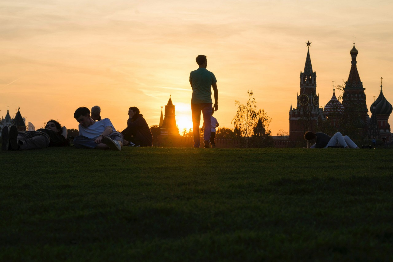 People sitting on green lawn with a view of Kremlin tower during the sunset