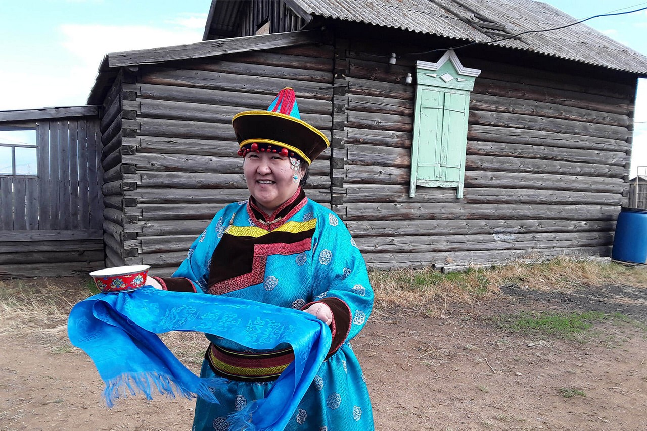 A Buryat woman wearing Buryat traditional clothes holding a scarf (hadak) and a plate in front of a wooden house