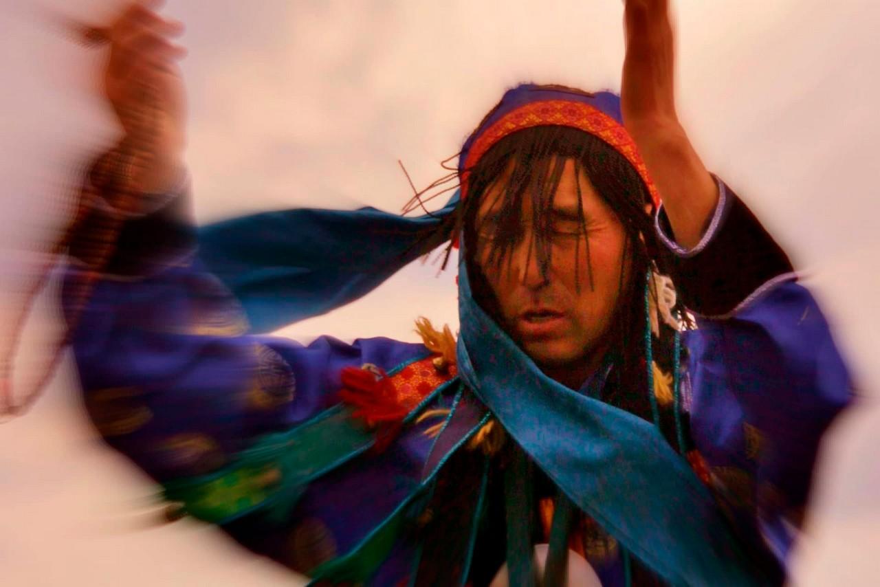 A Buryat shaman is dancing and performing a ritual