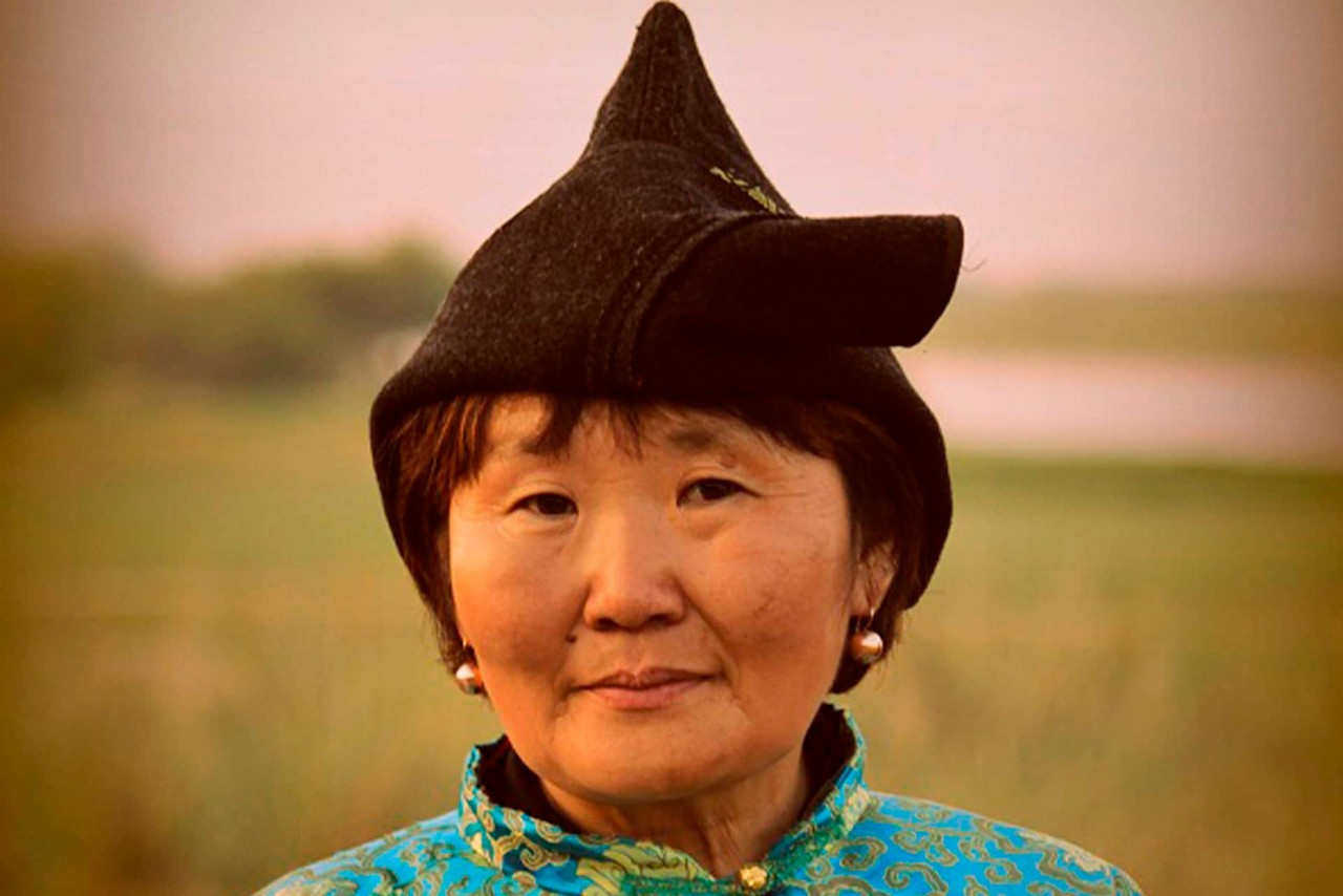 Face of a Buryat woman wearing traditional hat