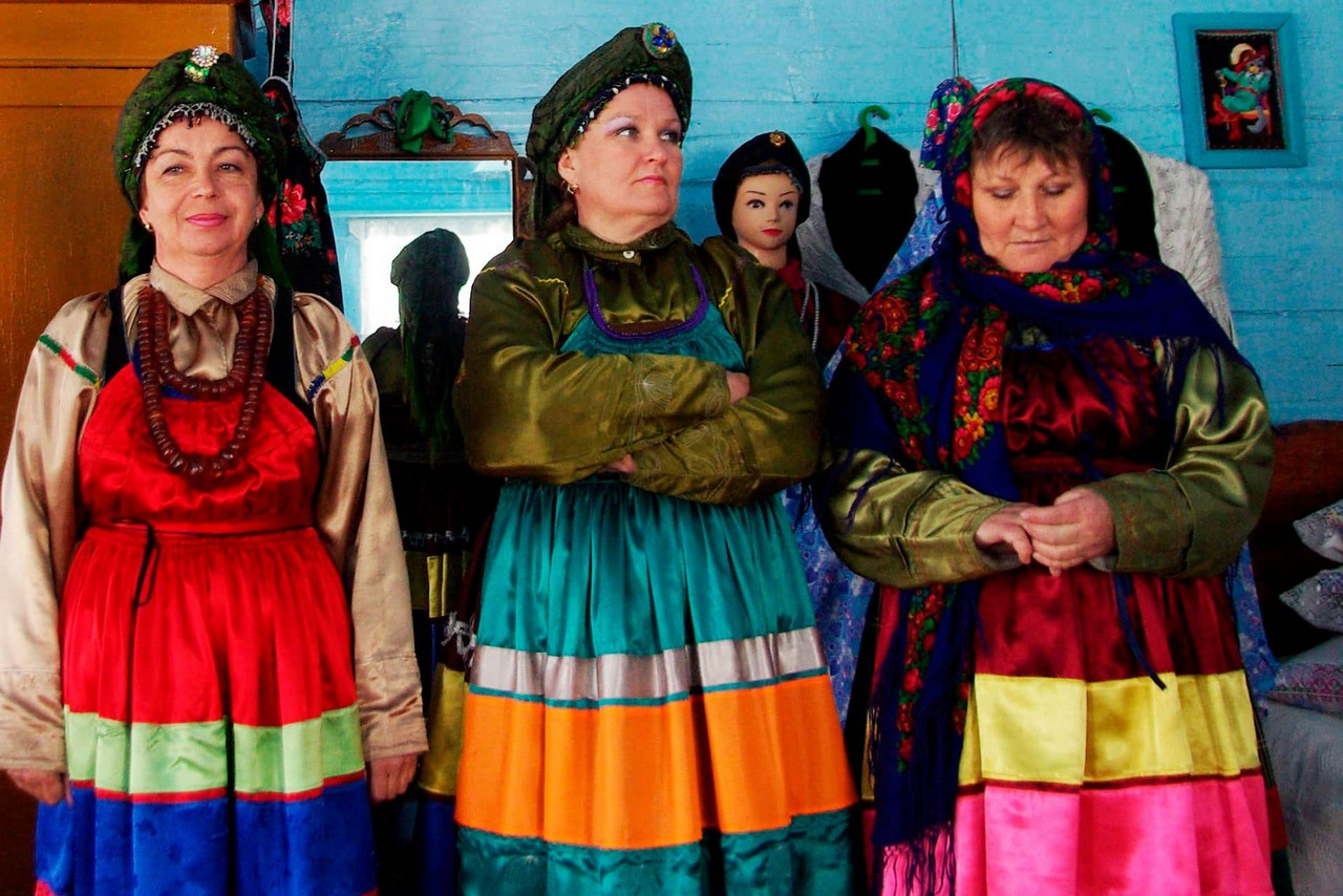 Old-believer women wearing traditional clothes in a wooden house