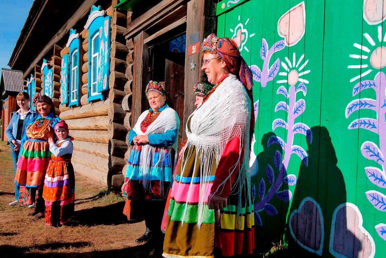 Old-believer women wearing traditional clothes in front of a wooden house decorated with hand painting