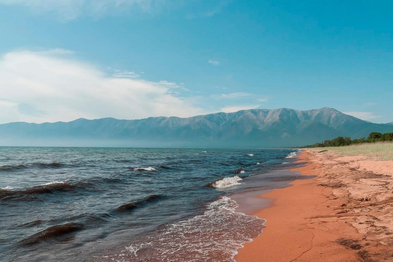 Sandy shore of lake Baikal and mountains behind it