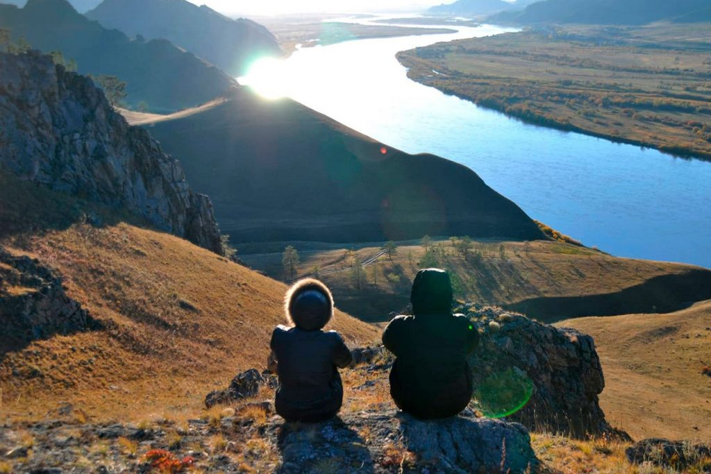 Two people seating on the top of a mountain enjoying the view over a river in the sunshine