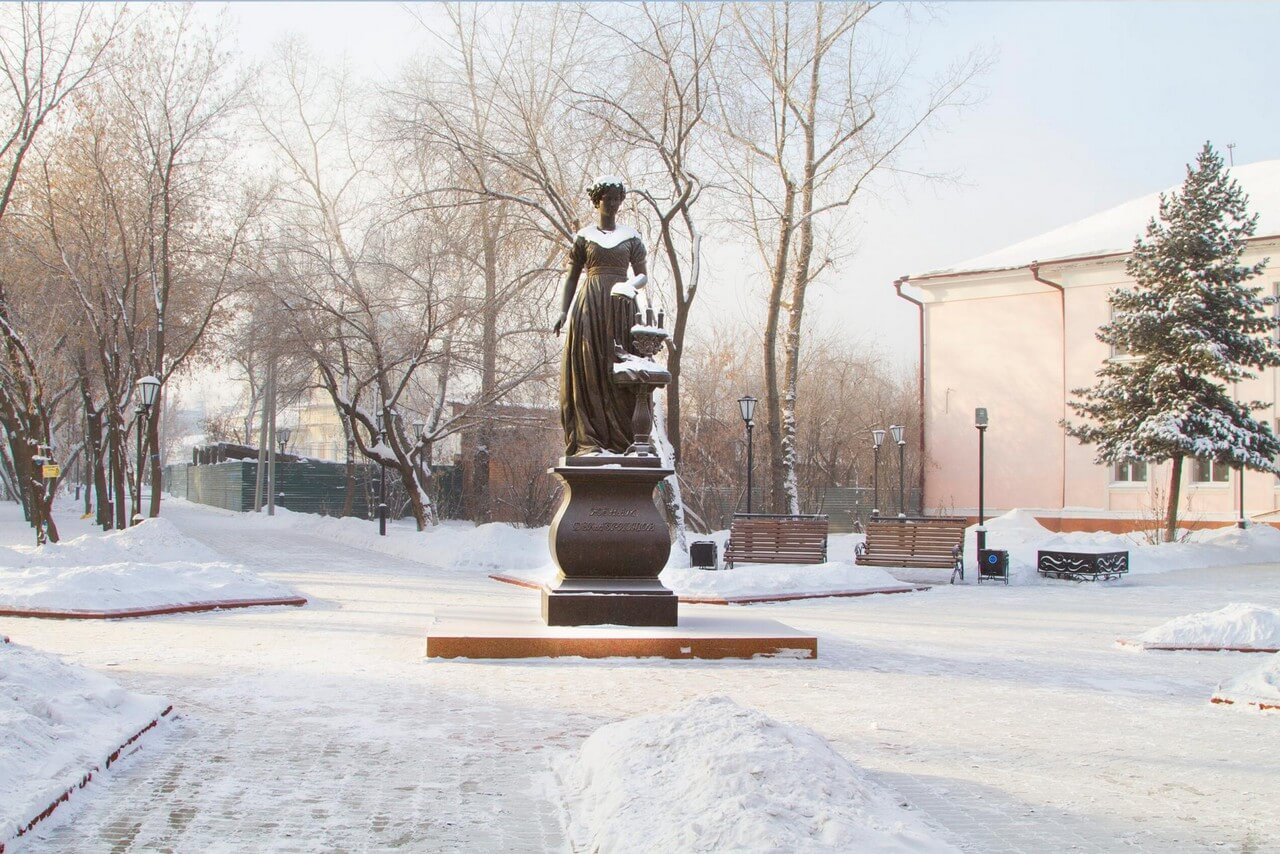A 3-meter high bronze statue of a woman of 19th century on a granite base, bronze chandelier with candles in front of a woman, in winter