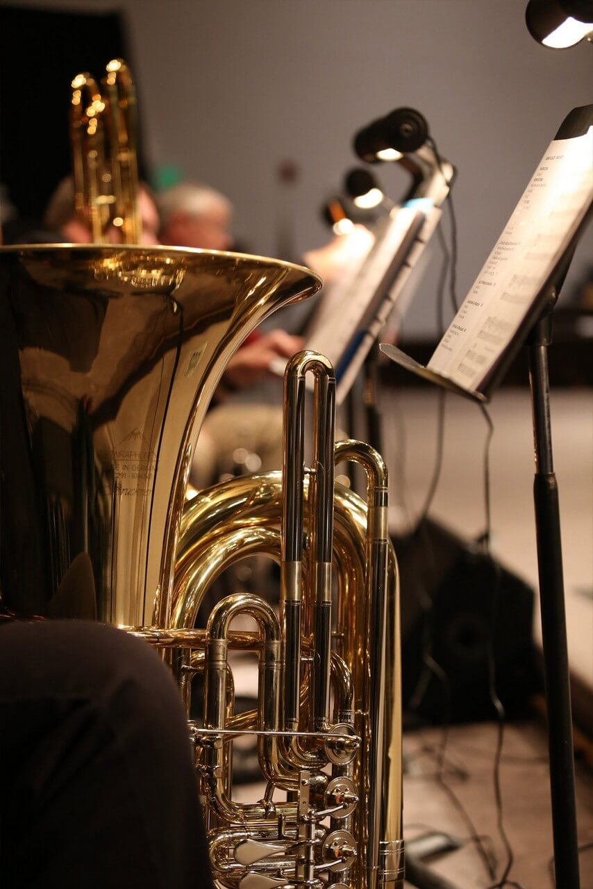Orchestra: a musician with a trumpet, music stand with music sheets