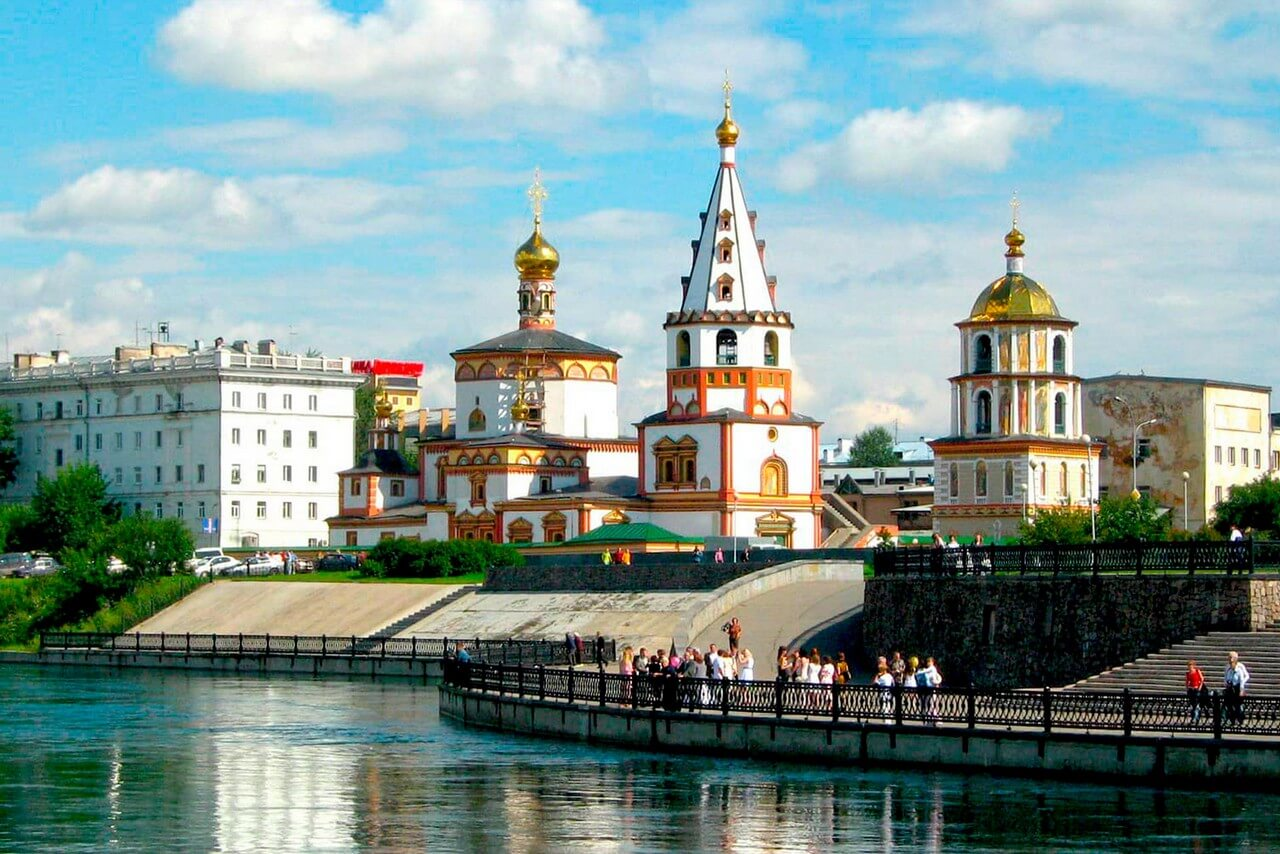 Renovated embankment of a river, colorful orthodox church near the river, buildings of soviet period and people walking on the embankment