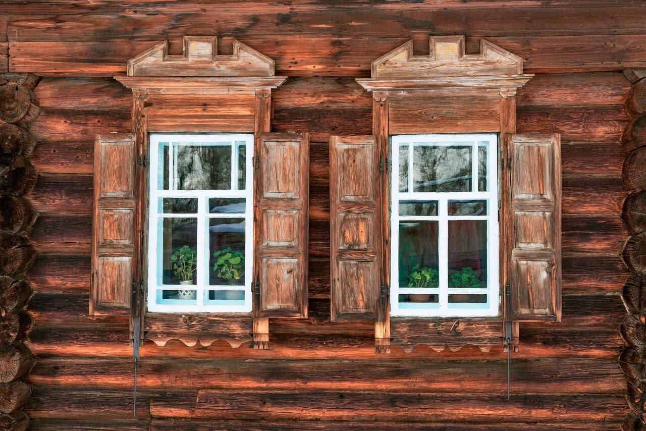 Two windows of a wooden house, storm shutter