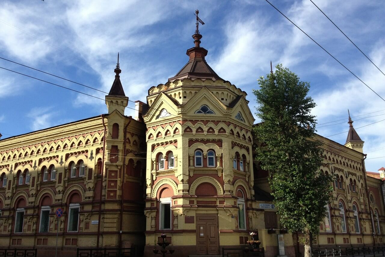 Red and yellow two-storey house in new russian style, house with towers, a wind vane on the top