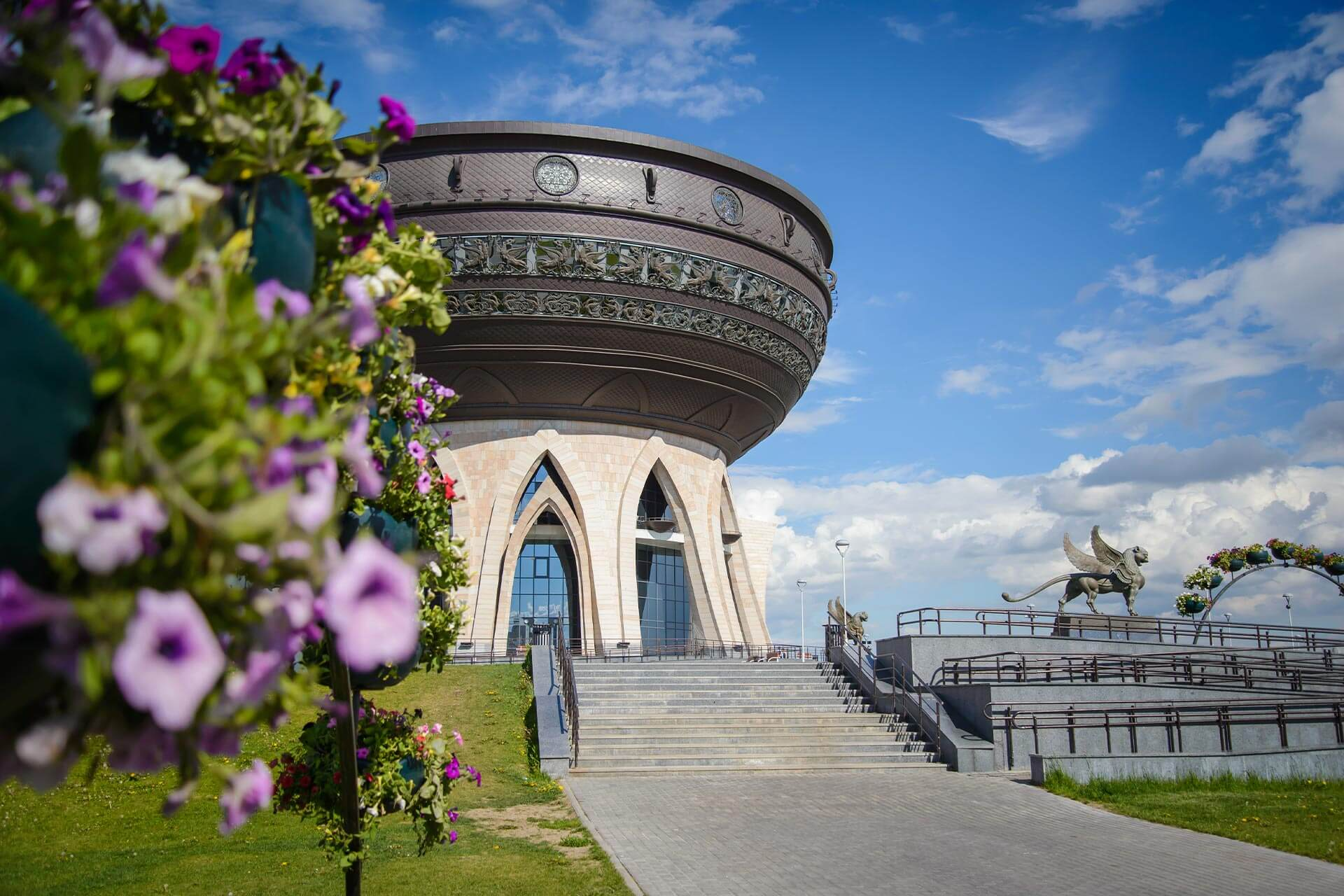 Round building of an unusual architectural style. The base of the building with gothic arch shaped windows. The top is in shape of a bowl or a copper. Flowers in front of the building