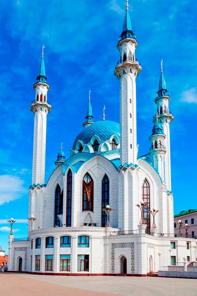 White mosque with a blue dome and four minarets.