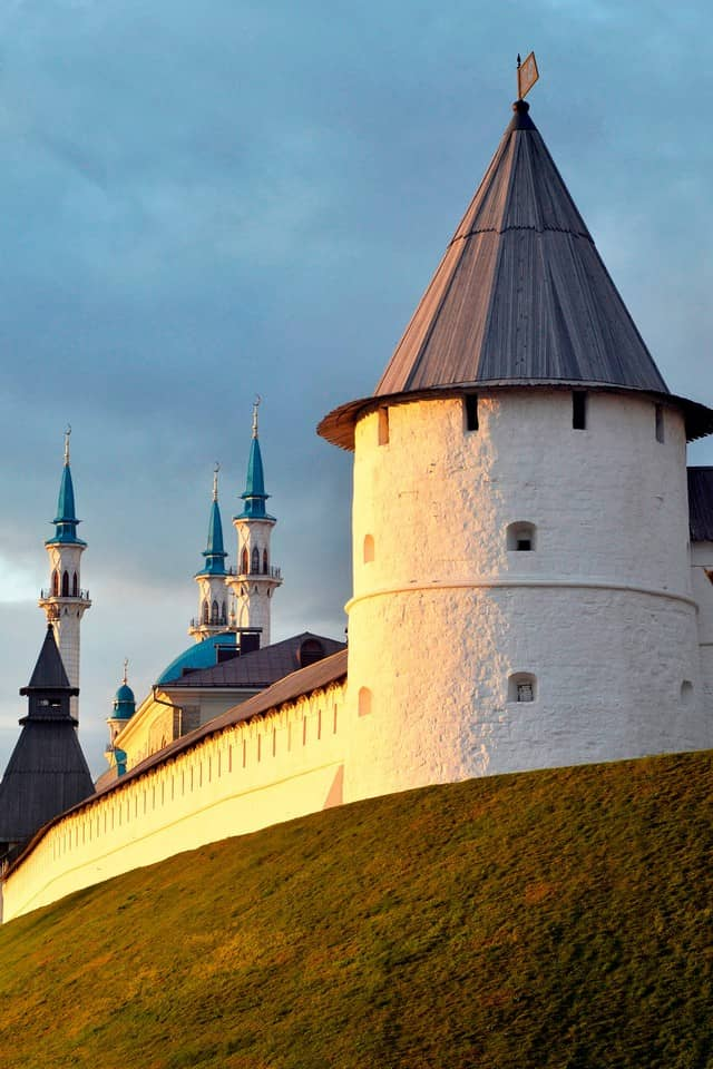 A white round tower with small windows and the view to a Mosque's white Minarets with blue tops.