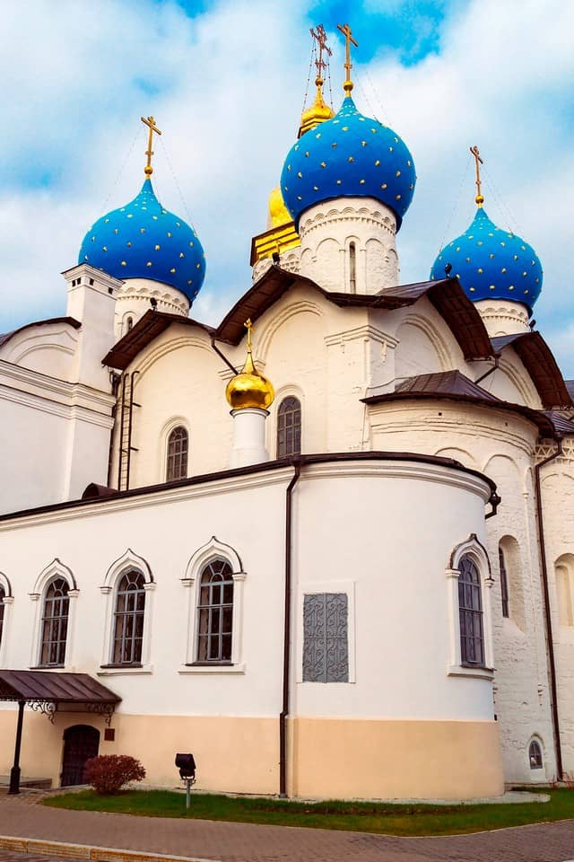 A white cathedral with blue and golden domes.