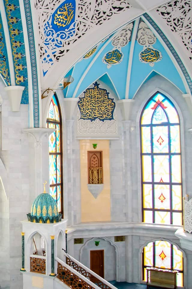 White marble walls with blue decorations inside of the mosque, arched ceiling.