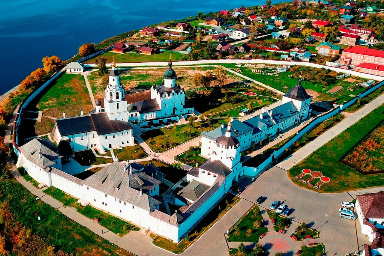 An Orthodox monastery consisting of white churches, buildings and walls.