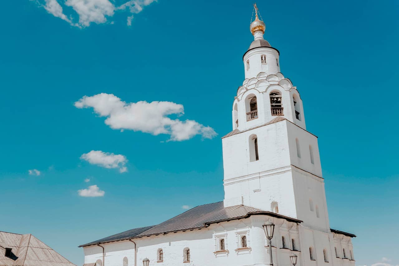 An Orthodox white church with a tall bell tower topped with a golden cupola
