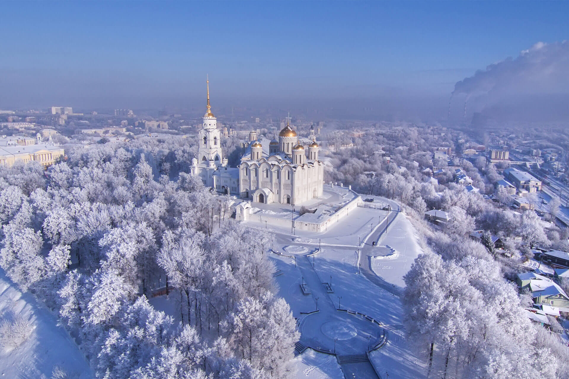 A view to a big white cathedral with golden domes from the bird-eye view in winter.