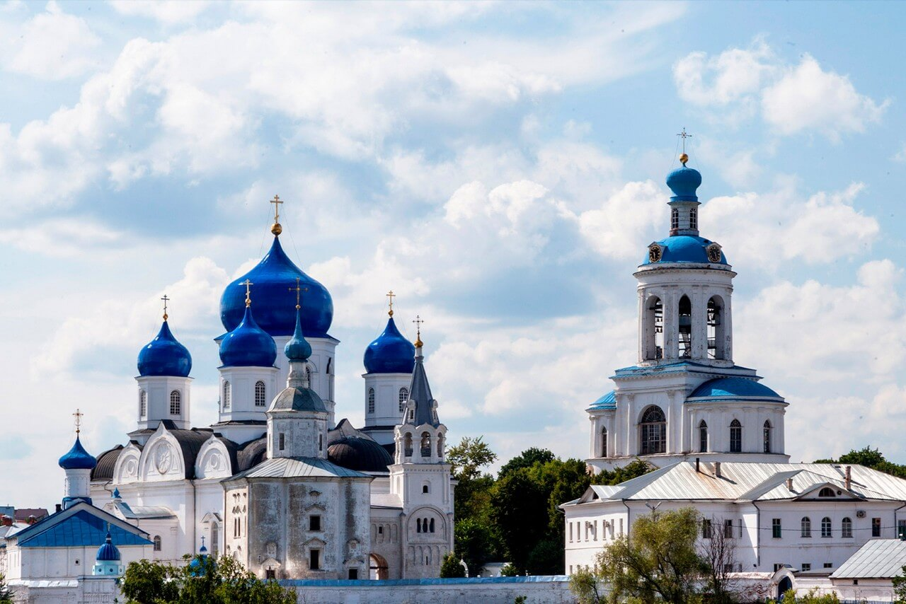 A white Orthodox cathedral with bright blue domes and a bell tower against the background of a gently blue sky.