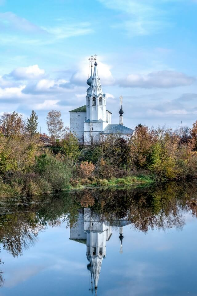 A white Orthodox church surrounded with autumn trees on the other side of a river.