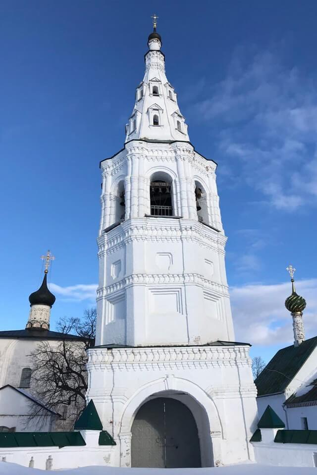 A white bell tower and two small domes of a church