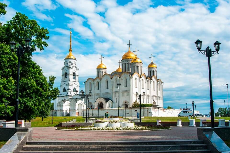A big white cathedral and a bell tower with golden domes.
