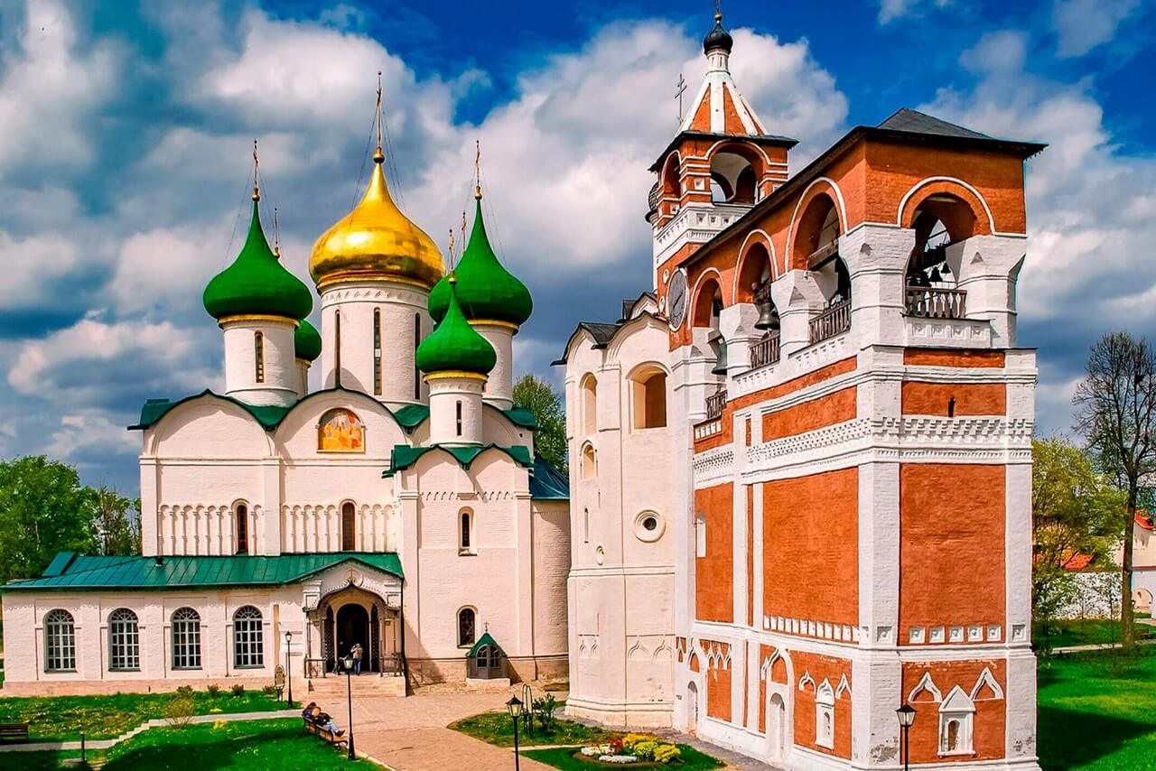 The Orthodox Church with gilded and green domes and the red-and-white monastery bell tower against a background of the blue sky.