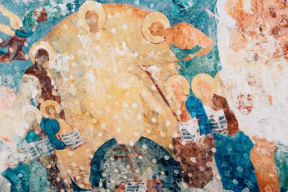 An ancient fresco in orthodox church presenting saints with golden nimbus.