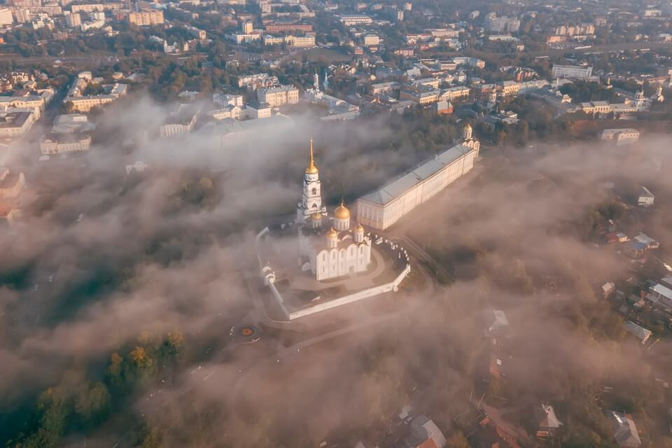 Aerial view on a big white Cathedral with golden domes in the fog.
