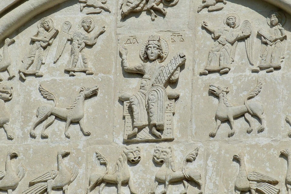 A decoration of a wall, carved saints with nimbus and mythic creatures.