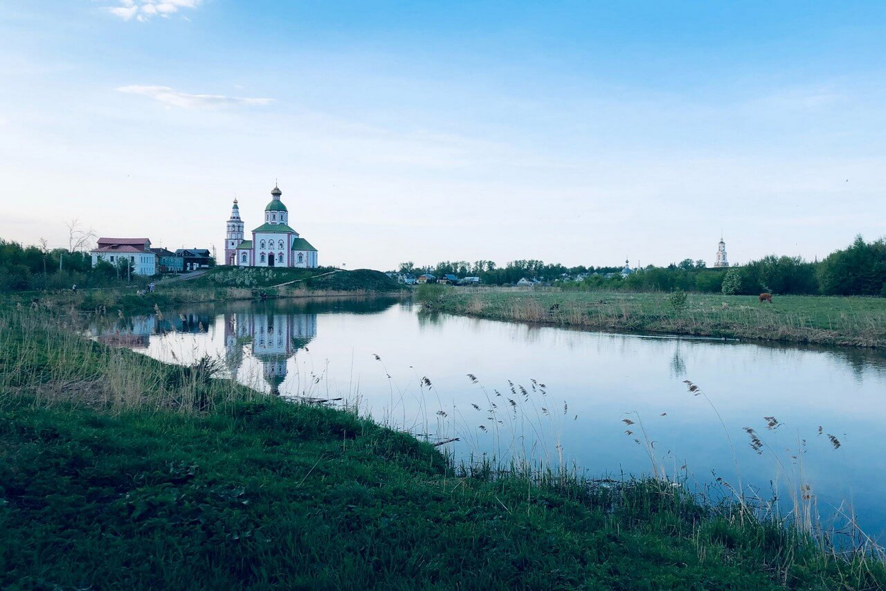 The white-red church with a green roof standing on the riverbank.
