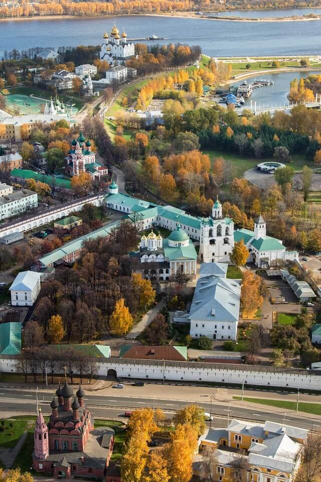 Monastery with white buildings, churches and green roofs, yellow and green autumn trees, river behind the monastery.