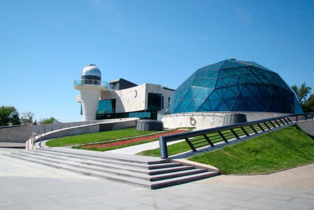 A complex of modern buildings of unusual architecture. A gray concrete building of modern architecture with a high round tower. The building in front is designed as a glass sphere.