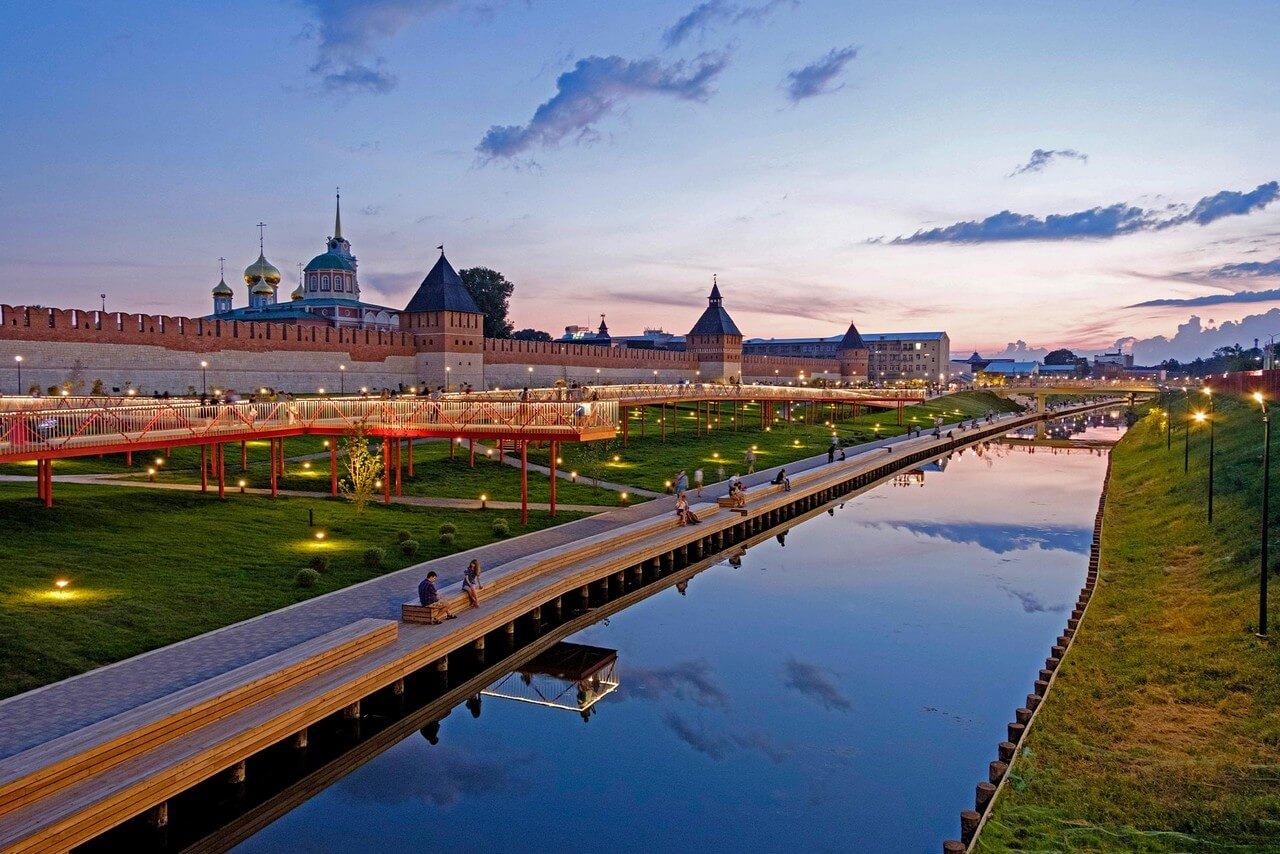 A river and people chilling on embankment in front of an ancient building of Tula Kremlin in late evening