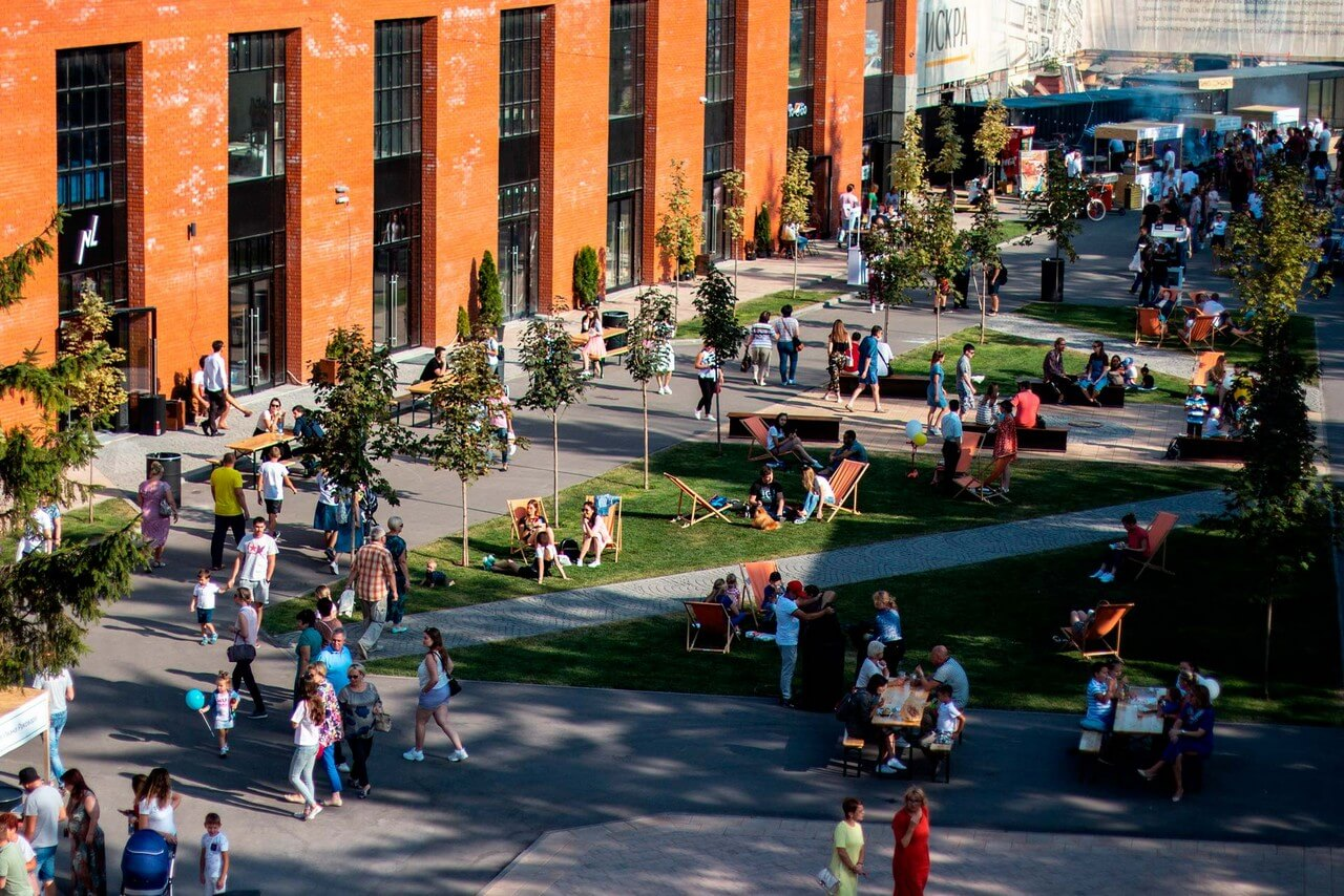A modern park with people walking in front of red brick building