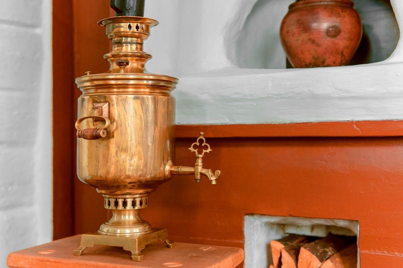 A bronze Tula samovar on the table, Russian stove