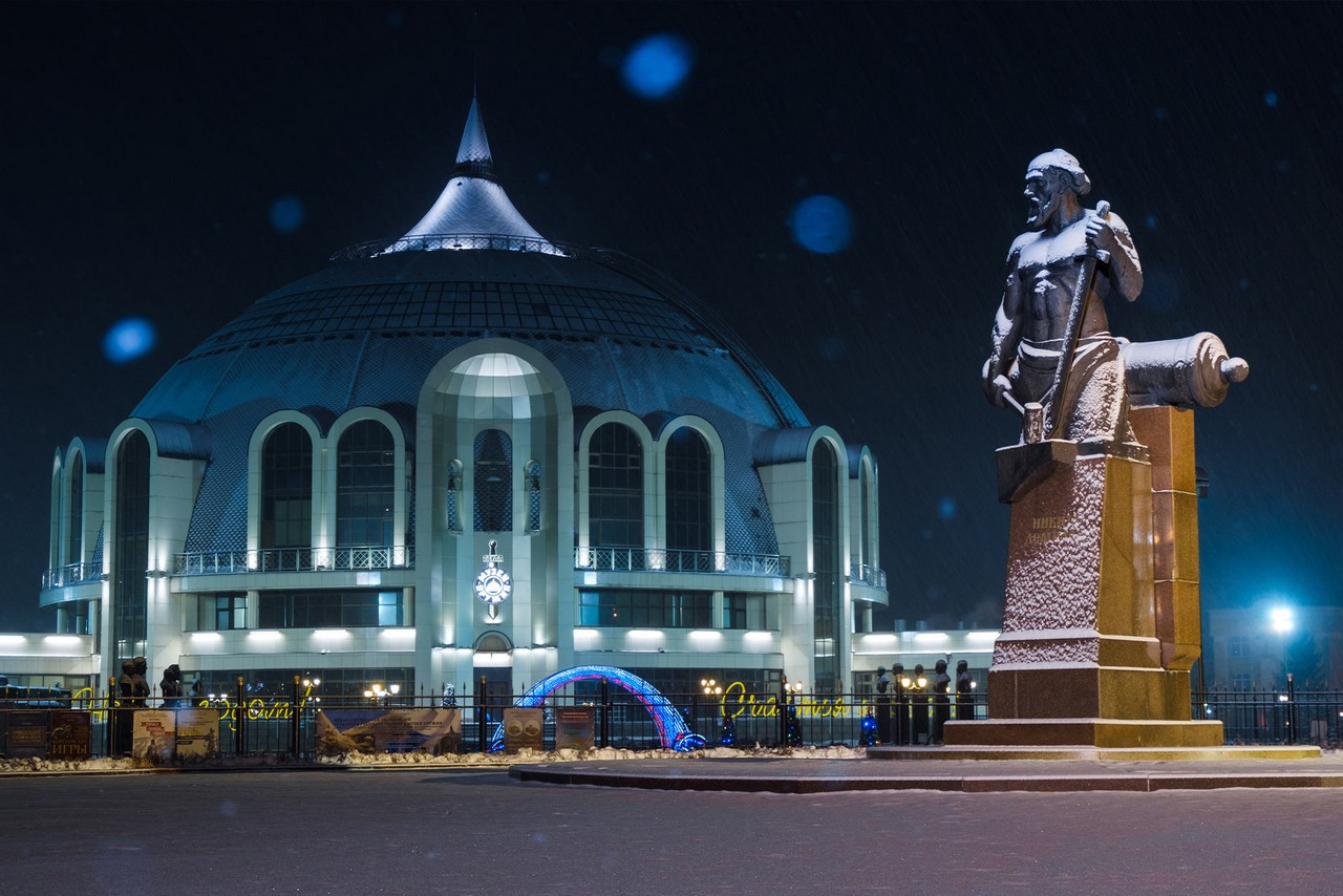 A building designed in the form of a large helmet, a statue in front of it