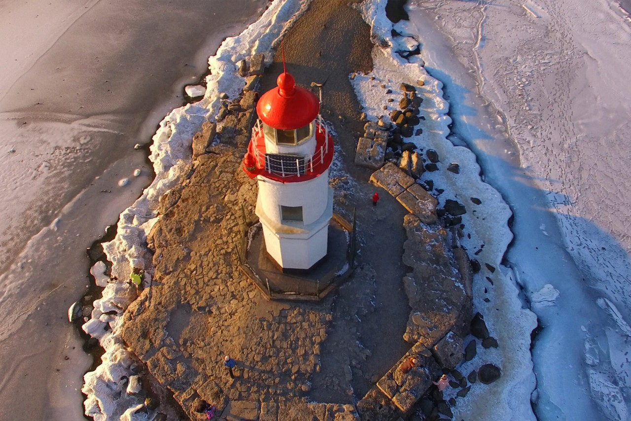 Aerial view of a lighthouse located on a small peninsula