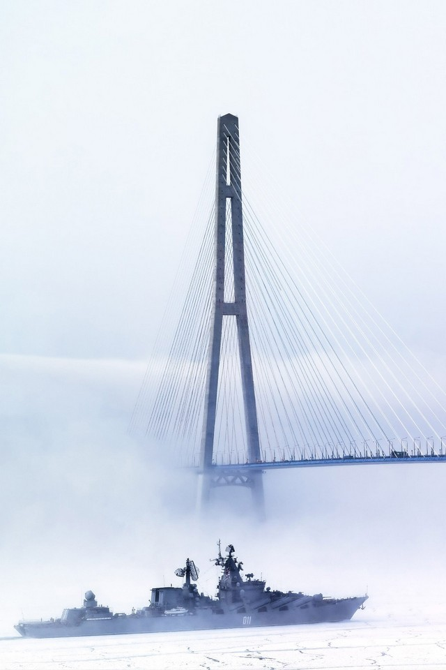 A naval ship in front of a cable-stayed bridge in fog