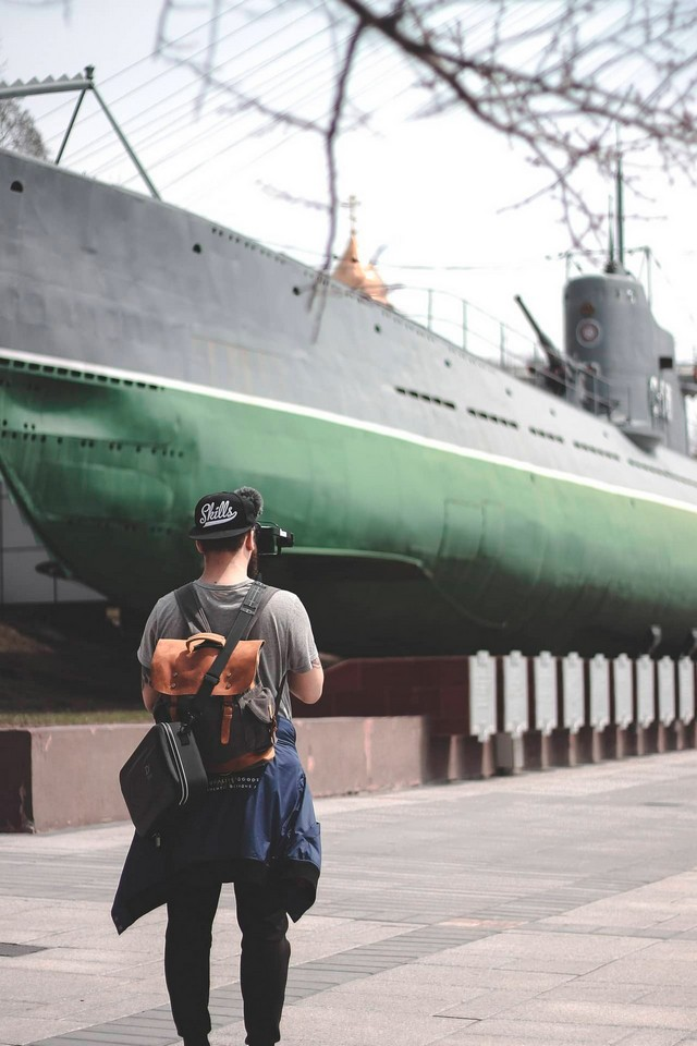 A young man wearing a cap in front of a submarine