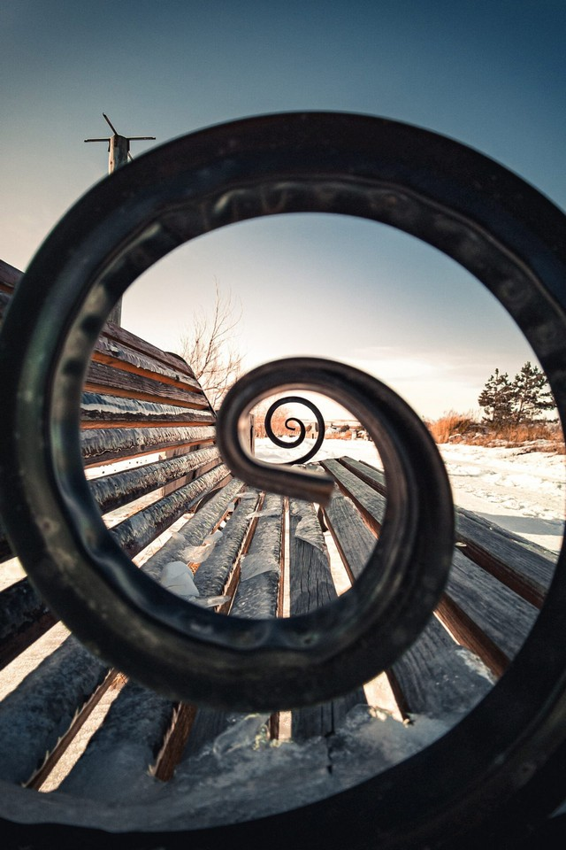 A metal arm of a bench made in a shape of spiral