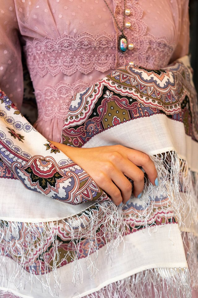 A lady wearing old traditional purple dress decorated with lace, enamel brooch, Russian foulard in hands of a woman